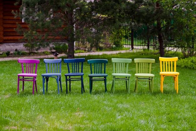 Een rij kleurrijke regenboog houten stoelen op een groen gazon een lgbt-gemeenschapsfeest in het park in de m...