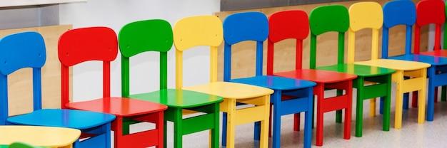 Een rij lege veelkleurige kinderstoelen