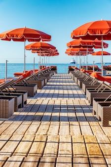 Een rij ligstoelen met oranje matrassen en parasols in een trendy resort.