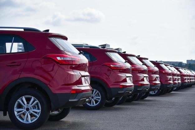 Een rij nieuwe rode auto's op straat