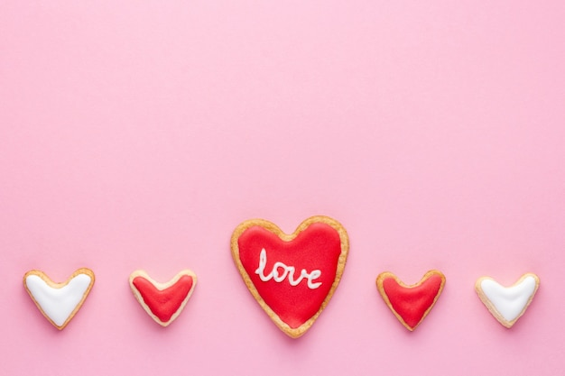 Een rij van hartvormige koekjes met suikerglazuur en woordliefde voor st valentine-dag op roze achtergrond