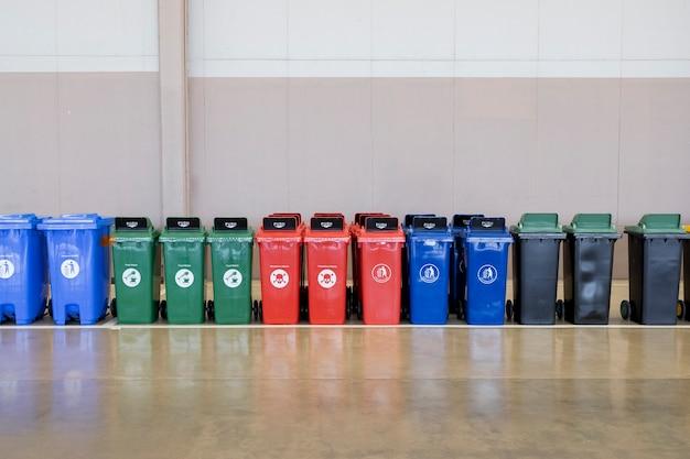 Een rij veelkleurige industriële plastic afvalcontainers.