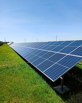 Een rij zonnepanelen staat op een groen veld, tegen de blauwe lucht. een symbool van schone energie, zorg voor het milieu, een concept.