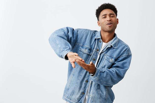 Een rijk leven leiden. positieve emoties. portret van jonge aantrekkelijke zwarte man met afro kapsel in wit t-shirt en spijkerjasje geld weggooien voor videoclip, plezier maken met vrienden