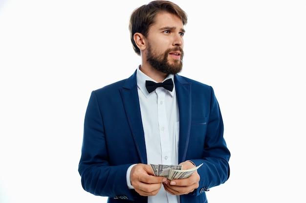 Een rijke man in een klassiek pak tegen een lichte achtergrond met een bundel geld in zijn handen. hoge kwaliteit foto