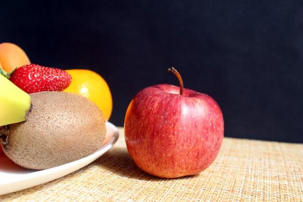 Een rijpe heerlijke appel ligt op tafel naast een bord met fruit en bessen op tafel, op een zwarte muur. hard direct licht.