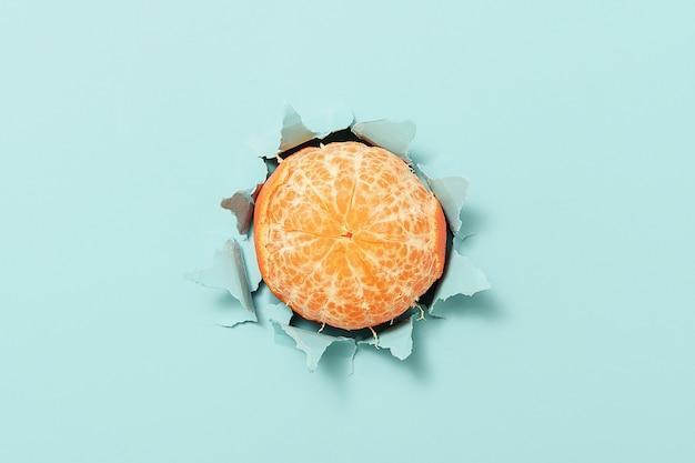 Een rijpe mandarijn door gescheurd blauw papier.