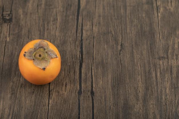 Een rijpe persimmon fruit geplaatst op houten oppervlak