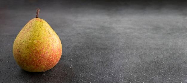 Een rijpe sappige peer op een grijze cementondergrond