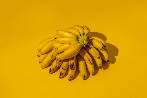 Een rijpe trendy kant-en-klare lelijke tros mini-bananen met zwarte stippen op een geel oppervlak