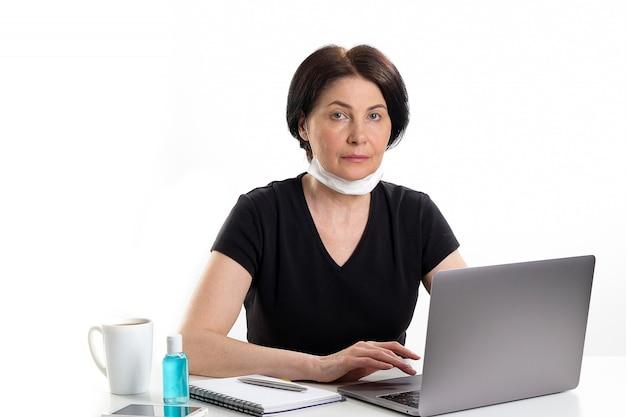 Een rijpe vrouw in een medisch masker werkt op een laptop. naast een mok koffie of thee, handdesinfecterend middel.