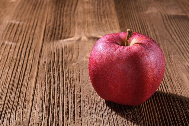 Een rode appel ligt op een getextureerde bruine houten tafel en werpt een harde schaduw, close-up.