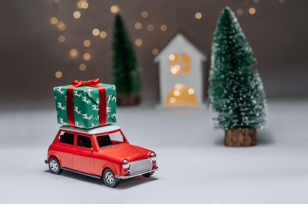Een rode auto op de achtergrond van een bos en een huis brengt kerst-nieuwjaarscadeaus.