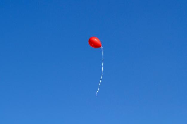 Een rode ballon vliegt omhoog in de blauwe lucht