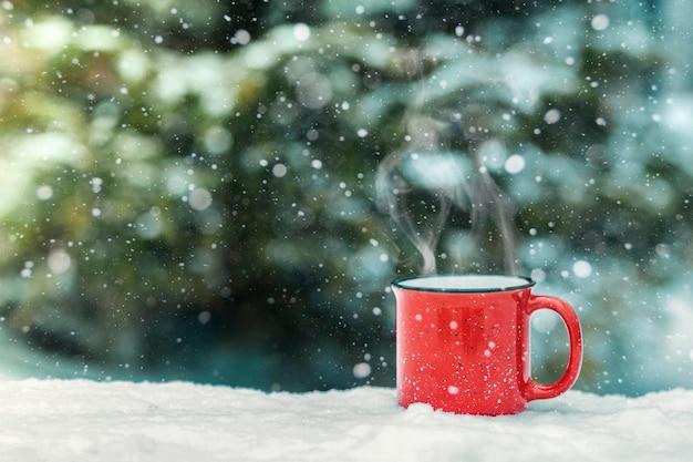 Een rode beker met een warme winterdrank (glühwein, cacao, koffie, thee) tegen de achtergrond van een winterbos en sneeuw. winterstemming en comfort.