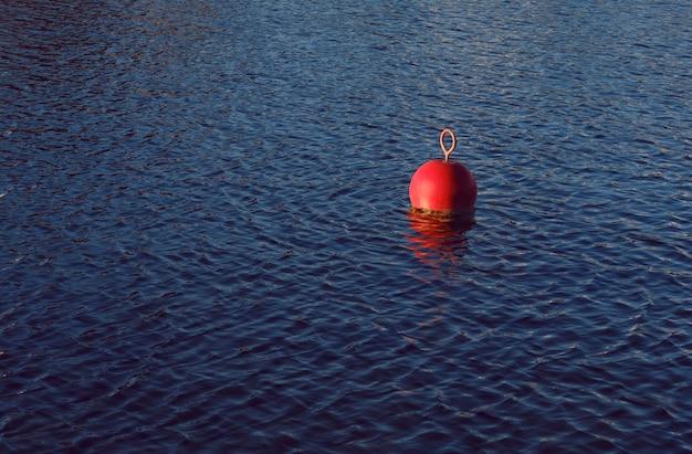 Een rode boei in de zee of het meer voor strandmarkering en mag de kanaallimiet niet overschrijden