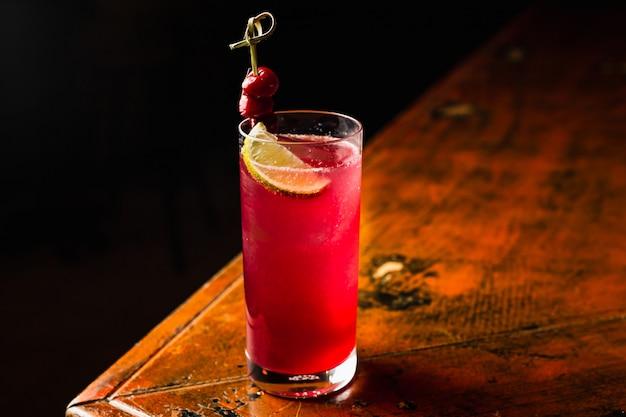 Een rode cocktail in een longdrinkglas gegarneerd met citroen en kersen