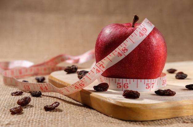Een rode dieetappel voor gewichtsverlies ligt op een houten plank op tafel, een centimeter gewikkeld in een meetlijn en rozijnen zijn willekeurig verspreid.