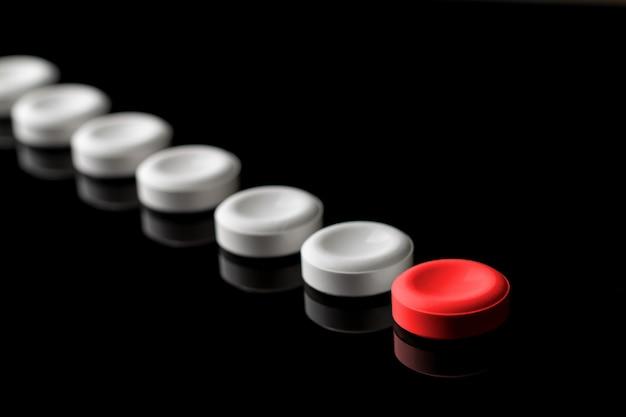 Een rode en veel witte pillen op een zwarte achtergrond. met onscherpte in perspectief.
