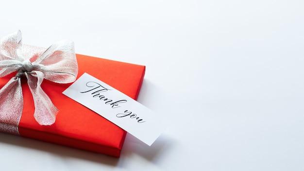 Een rode geschenkdoos met grijze tape en een briefje met bericht