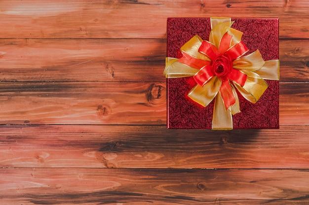 Een rode geschenkdoos op een natuurlijke houten bordachtergrond voor kopieerruimte, bovenaanzicht en close-up, feestelijke stemming om te geven en te delen.