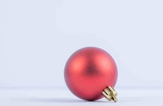 Een rode glinsterende of glanzende eikenboombal op een witte Gratis Foto