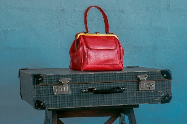 Een rode handtas staat op een vintage reiskoffer tegen een blauwe betonnen muur