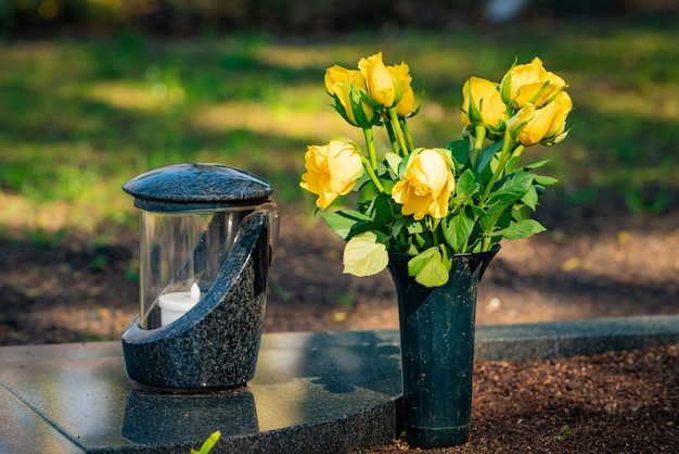 Een rode kaars op de grafstenen met bloemen