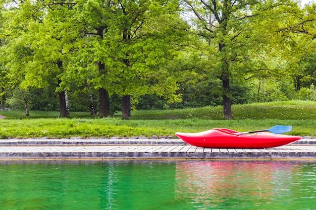 Een rode kajak op houten steiger in een meer