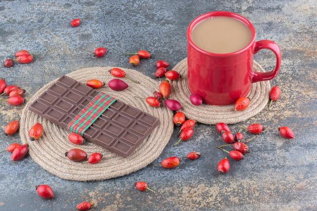 Een rode kop drank met chocolade en rozenbottels op marmeren achtergrond. hoge kwaliteit foto