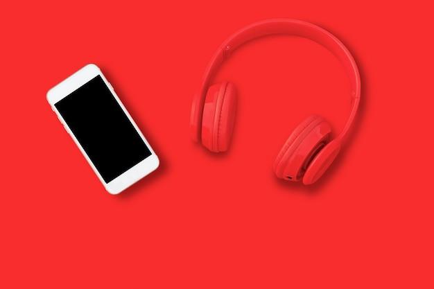 Een rode koptelefoon, bovenaanzicht van koptelefoon en smartphone op rode tafel.