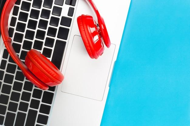 Een rode koptelefoon, bovenaanzicht van rode koptelefoon met laptop toetsenbord