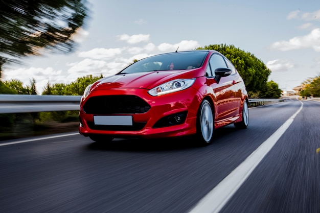 Een rode minicoupé die met hoge snelheid op de snelweg rijdt.