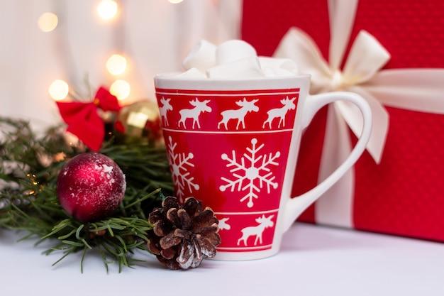 Een rode mok met marshmallow een tak van een kerstboom speelgoedbal kegel en geschenkdoos decoraions