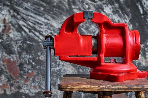 Een rode oude bankschroef is bevestigd aan een houten plank
