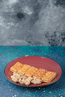 Een rode plaat met gezonde noten en heerlijke crackers op melkwegtafel.