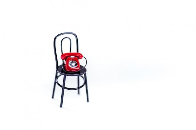 Een rode retro telefoon op zwarte stoel. valentijnsdag concept. bel mij.