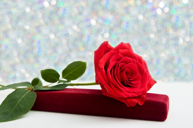 Een rode roos en sieraden aanwezig doos met boke achtergrond