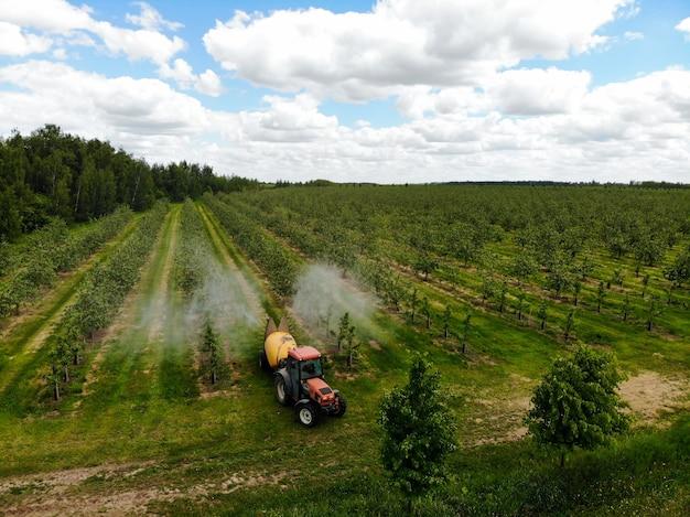 Een rode tractor spuit pesticiden in een appelboomgaard en spuit een appelboom met een tractor