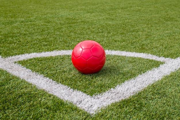Een rode voetbal ligt in de hoek van het voetbalveld naast de lijn