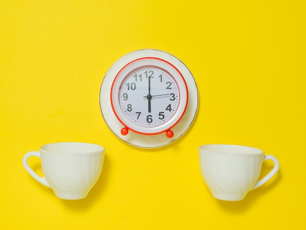 Een rode wekker op een schotel en twee koffiekopjes op een gele achtergrond. het concept van het opheffen van de toon in de ochtend. plat leggen.