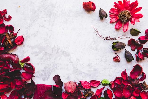 Een rode welriekend mengsel van gedroogde bloemen en kruidenriem tegen witte geweven achtergrond