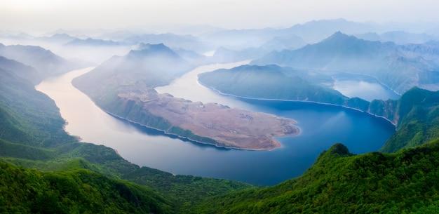 Een rokerig landschap van rivieren en bergen.