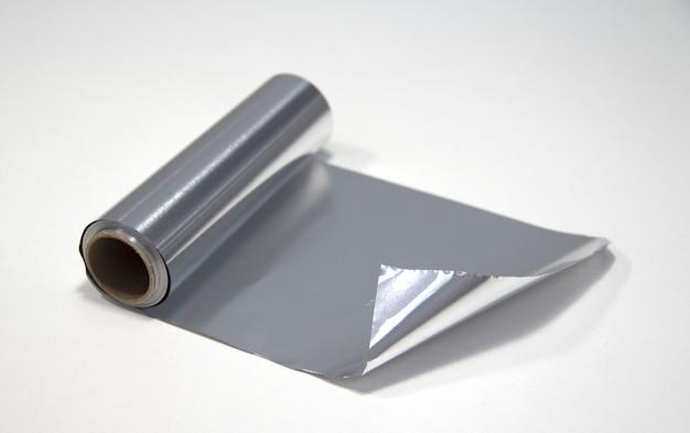 Een rol aluminiumfolie op een witte achtergrond. folie voor de kapper