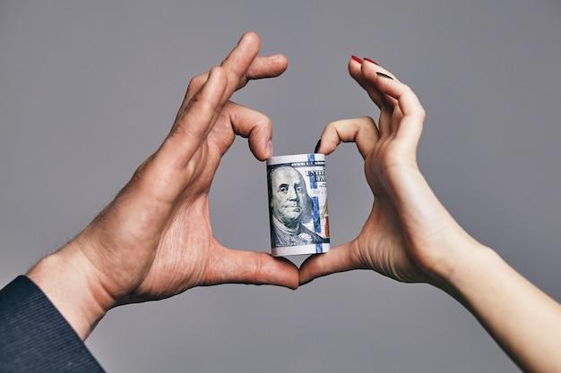 Een rol dollars met het hart gemaakt van twee handen