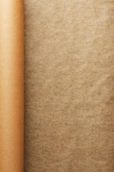 Een rol ontvouwen bruin perkamentpapier, voor het bakken van voedsel op een donkere achtergrond, bovenaanzicht.