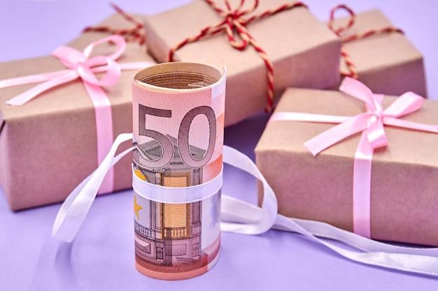 Een rol van 50 euro biljetten met lint tegen geschenkdozen