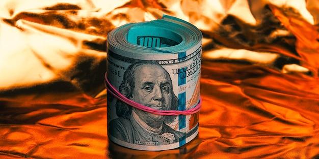Een rol van honderd amerikaanse dollars in close-up op een gouden achtergrond een grote stapel contante dollars