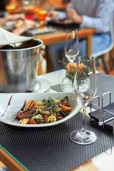 Een romantisch diner in de zomer op het dek van het schip op de bodem m met twee glazen witte wijn en een wijnkoelkast.