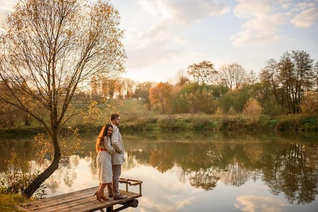 Een romantisch jong stel staat op een pier in de buurt van het meer. vallen.